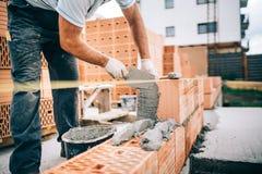 fabrieksarbeider, metselaar die bakstenen installeren op bouwwerf stock afbeeldingen