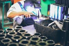 Fabrieksarbeider in productieinstallatie het malen om een Metaalpijp te beëindigen royalty-vrije stock afbeeldingen
