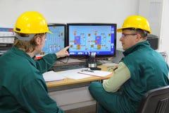 Fabrieksarbeiders in controlekamer stock foto