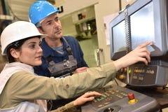 Fabrieksarbeiders die aan machnery werken stock fotografie