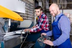 Fabrieksarbeiders die aluminiumkaders snijden stock afbeeldingen