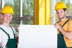 Fabrieksarbeiders die een witte raad houden stock foto's