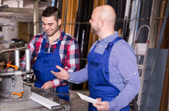 Fabrieksarbeiders die vensterprofielen snijden Stock Foto's