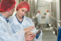 Fabrieksarbeiders in workshop die digitale tablet gebruiken stock afbeeldingen
