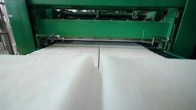 Fabrieksmachine die witte stof op een transportband spoelen stock videobeelden