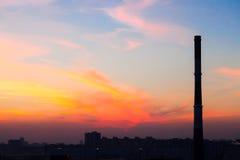 Fabriekspijp in de stad bij een mooie zonsondergang Royalty-vrije Stock Foto