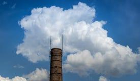 Fabrieksschoorsteen tegen de blauwe hemel en de witte wolken Stock Afbeelding