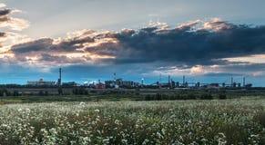 Fabrik på solnedgången med gräs Arkivfoto