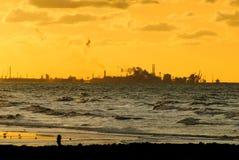 Fabrik am Strand an der goldenen Stunde Stockbilder