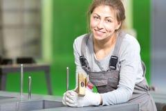 Fabrikarbeitnehmerin während des Magnetkernzusammenbauens des Transformators Stockfotografie