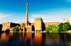 Fabrikgebäude auf Fluss Stockfoto