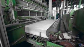 Fabrikmaschinen rollen eine Schicht synthetisches Gewebe stock footage