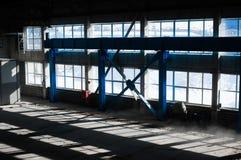 Fabriks- fabrik Tom hangarbyggnad tonad bakgrundsblue Produktionrummet med stora fönster och metallstrukturer Arkivfoton