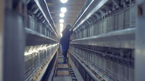 Fabriksanställd klättrar en stege till kontrollen behandla som ett barn på hönor på överkant-sidan lager videofilmer