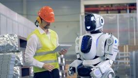 Fabriksanställd meddelar med en humanoid i gester arkivfilmer