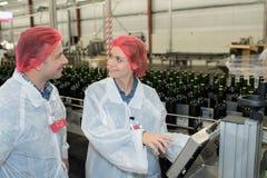 Fabriksarbetare i växt för vattenflaska arkivfoton
