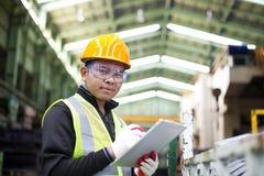 Fabriksarbetare med skrivplattan på handen