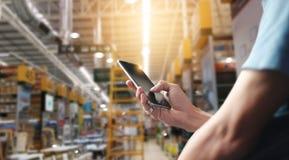 Fabriksarbetare som använder applikation på den fungeringsmobila smartphonen royaltyfri fotografi