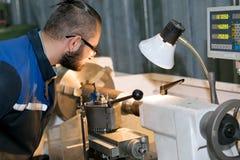 Fabriksarbetare som arbetar på drejbänkmaskinen Royaltyfri Bild