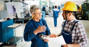 Fabriksarbetare som diskuterar data med arbetsledaren i metallfabrik arkivbilder