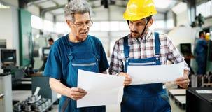 Fabriksarbetare som diskuterar data med arbetsledaren i metallfabrik arkivbild