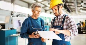 Fabriksarbetare som diskuterar data med arbetsledaren i metallfabrik arkivfoton
