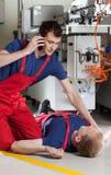 Fabriksarbetare som kallar för hjälp efter olycka Arkivbild