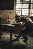 Fabriksarbetare som maler skoformen arkivfoto