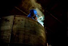Fabriksarbetare som svetsar en behållare royaltyfri fotografi