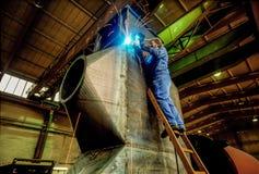 Fabriksarbetare som svetsar en filterbehållare arkivfoton