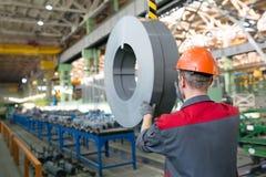 Fabriksarbetare som transporterar last med kranen Fotografering för Bildbyråer