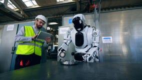 Fabriksarbetaren kontrollerar en cyborg som polerar en metalldiskett arkivfilmer