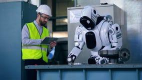 Fabriksarbetaren kontrollerar en polerande metall för robot stock video