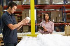 Fabriksarbetaren och chefen som kontrollerar godor på produktion, fodrar royaltyfri fotografi