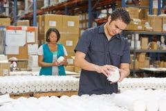 Fabriksarbetaren som kontrollerar godor på produktion, fodrar arkivfoton