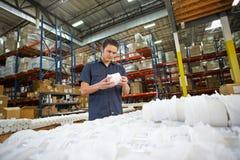 Fabriksarbetaren som kontrollerar godor på produktion, fodrar Royaltyfri Fotografi