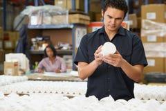 Fabriksarbetaren som kontrollerar godor på produktion, fodrar royaltyfri bild