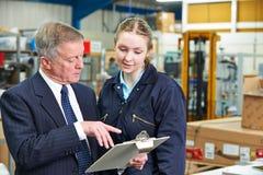 Fabrikschef And Apprentice Engineer som ser skrivplattan Royaltyfri Bild