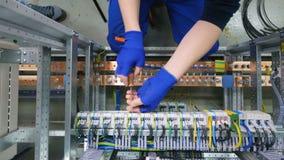 Fabrikselektrikerteknikern som installerar kablar med skruvmejsel, drar åt muttern i electical askkontrollkabinett in i lager videofilmer
