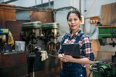 Fabrikskvinna som rymmer den digitala minnestavladatoren Royaltyfri Bild