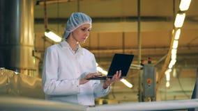 Fabrikslätthet med en damspecialist som fungerar en bärbar dator stock video