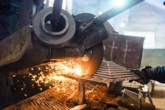 Fabriksmakthjälpmedel som används av arbetaren för att mala och att klippa stål Arkivbild