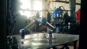 Fabriksmaskinen roterar på en metalltabell som arbetar arkivfilmer