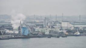 fabriksrör med rök nära port fotografering för bildbyråer