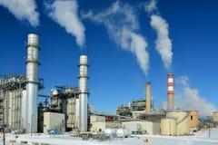 Fabriksskorsten för kolfossila bränslenkraftverk sänder ut koldioxidförorening på en kall snöig dag Royaltyfria Bilder