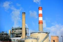Fabriksskorsten för kolfossila bränslenkraftverket med röda och vit färgade band sänder ut koldioxidförorening Royaltyfri Fotografi