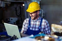 Fabriksteknikern kontrollerar kvaliteten av den tillverkade delen arkivfoto
