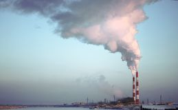 Fabrikziegelsteinkamin Der Rauch von der Rohr Cogenerationsanlage Dampf, der von einer Trompete auf dem Himmelhintergrund entgeht stockfotos