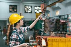 Fabryczny żeński pracownik przystosowywa łańcuszkowych żurawie Zdjęcia Royalty Free