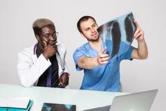 Fabrykuje mieć rozmowę z jego kolegą i trzymać xray w medycznym biurze biura medycznego obrazy royalty free